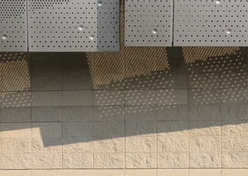 Detail of the facade and shadows cast through the perforated metal.