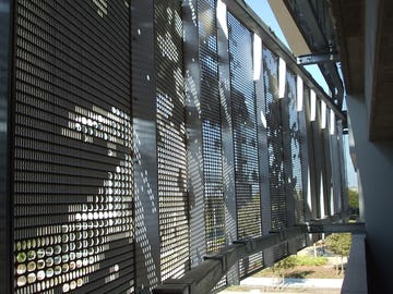 Detail of the perforated aluminum facade system from within the garage.
