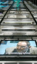 Video screens show Thom Mayne of Morphosis underneath the glass flooring.
