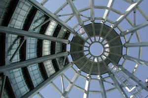 Upward view from inside the cone during the construction of Museum of Glass. The left side of this picture, photographed during construction, shows the final surface of the exposed panels.  The right side of the photograph shows the the sky filtered through the unfinished understructure of the cone.