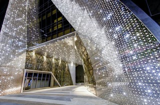 Harim Group Headquarters entrance has a curving stainless steel facade system made by Zahner.