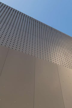 Custom dimpled panels extend the aesthetic established by the louvered perforated panels.