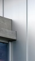 Custom metal details where aluminum wall panels meet concrete slab