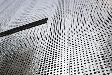 Detail of the custom perforated facade for Fairmont Pacific Rim.