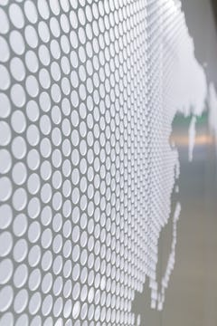 Detail of the perforated metal, painted grey on its exterior and white on its interior.