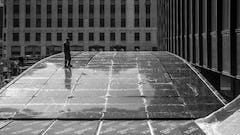Construction photo shows a man standing on the top of the Michigan Avenue Plaza awning in Chicago.