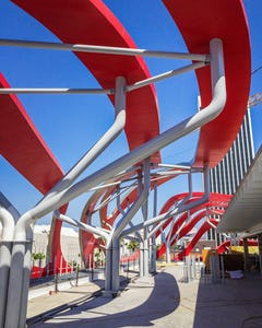 "Painted tubular steel ""trees"" were designed by Zahner engineers to support the curving ribbons, on the building's roof and facade."