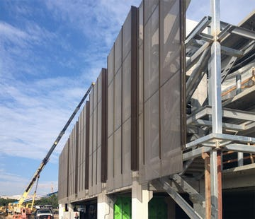 Construction photo of the perforated metal panel screen system at Stanford University Parking Garage.