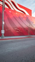 A perforated parking garage facade continues the stainless steel ribbon motif.