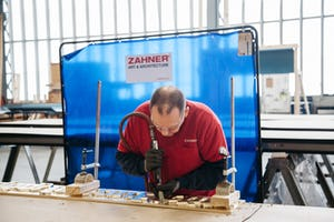 A Zahner craftsman applies a needle finish to a panel background.