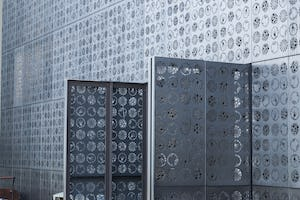 Operable doors clad in the Zahner perforated metal open to the ocean bay.