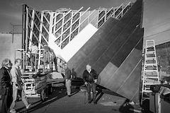 History of Fisher Center: The Design Team looks at the dual curvature metal panel system at A. Zahner Company Headquarters | Bard College student sign 'Make huge silver crumpled buildings, not war.'