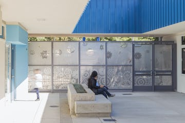"North entrance with perforated images of ""gears"" which represent the STEAM program at Washington Elementary."