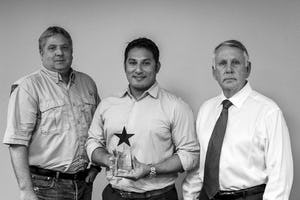 Tony Zuniga, Project Engineer (center), accepts the award for Pollution Prevention (P2) with Danny Jett, General Foreman (left), presented by Tom Cox, Deputy City Manager of Grand Prairie, Texas.