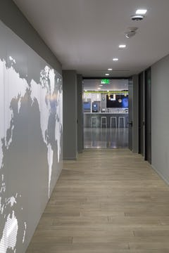 Backlit perforated metal serves as an accent wall between corporate spaces.